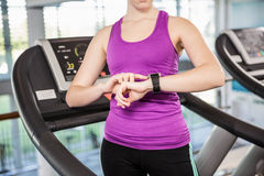 Mid section of fit woman using smartwatch on treadmill Stock Images