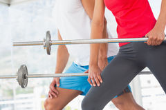 Mid section of fit young couple holding barbells Stock Photos