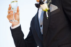 Mid section of flowers on lapel of male as he holds champagne glass Stock Photos