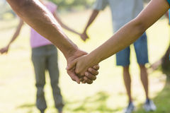 Mid section of friends holding hands in park Stock Image