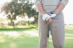Mid section of golfer standing with club Stock Photography