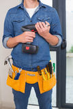 Mid section of a handyman with drill and toolbelt Royalty Free Stock Photography