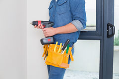 Mid section of a handyman with drill and toolbelt Stock Photography