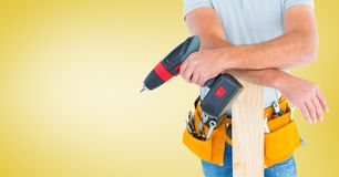 Mid section of handyman holding drill machine and plank. Against yellow background Stock Photos