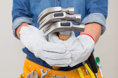 Mid section of a handyman holding hammers with toolbelt around waist Royalty Free Stock Photography