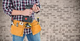 Mid section of handyman with tool belt and drill machine Royalty Free Stock Photo