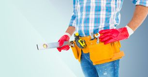 Mid section of handyman with tool belt and spirit level Stock Photo