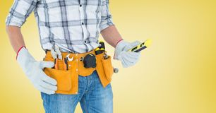 Mid section of handyman with tool belt and spirit level Royalty Free Stock Images