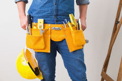 Mid section of handyman with toolbelt and hard hat Royalty Free Stock Photo
