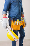 Mid section of a handyman with toolbelt and hard hat Stock Image