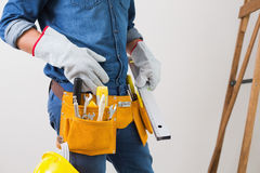 Mid section of a handyman with toolbelt and hard hat Stock Photography