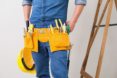 Mid section of a handyman with toolbelt and hard hat Royalty Free Stock Photo