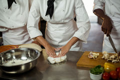 Mid section of head chef making pizza dough. In commercial kitchen stock image