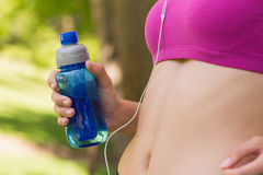 Mid section of healthy woman in sports bra with water bottle in park Royalty Free Stock Photo