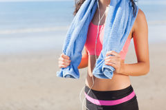 Mid section of healthy woman with towel around neck on beach Royalty Free Stock Image
