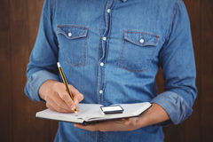 Mid section of hipster with mobile phone writing on book. Against wooden wall Stock Photo
