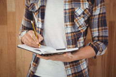 Mid section of hipster writing with pencil on book Royalty Free Stock Photos