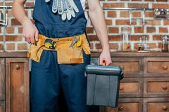 Mid section of home master with tool belt. Holding toolbox stock photo