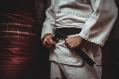 Mid section of karate player tying his belt Royalty Free Stock Photos