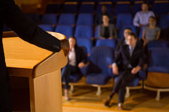 Mid section of male business executive giving a speech. At conference center Stock Photos