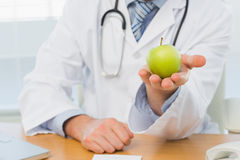 Mid section of a male doctor holding an apple Royalty Free Stock Images
