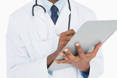 Mid section of a male doctor writing on clipboard Royalty Free Stock Photography