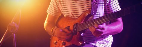 Mid section of male guitarist performing. At concert in nightclub Stock Photo