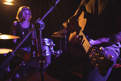 Mid section of male guitarist performing with female drummer. In nightclub Stock Image