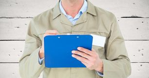 Mid section of male supervisor writing on clipboard. Against wooden background Royalty Free Stock Images