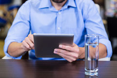 Mid-section of male therapist using digital tablet. In clinic Stock Image