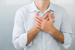 Mid section of a man with chest pain. Close up mid section of a young man with chest pain Royalty Free Stock Image