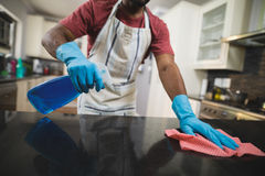 Mid section man cleaning marble counter in kitchen Royalty Free Stock Images