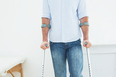 Mid section of a man with crutches in medical office Stock Photography
