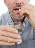 Mid section of a man with glass of water and pill Stock Image