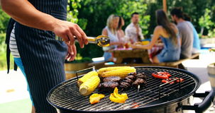 Mid section of man grilling corn, meat and vegetable on barbecue