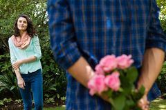 Mid-section of man hiding flowers behind back Stock Photos