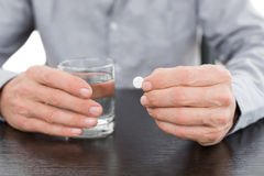 Mid section of a man holding glass of water and pill Royalty Free Stock Images