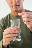 Mid section of a man holding glass of water and pill Royalty Free Stock Image