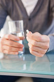 Mid section of a man holding glass of water and pill Stock Image