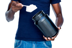 Mid section of man holding a scoop of protein mix Stock Photography