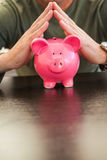 Mid section of a man with joined hands on piggy bank Stock Photography