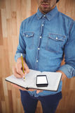 Mid section of man with mobile phone writing on book. Against wooden wall Stock Images