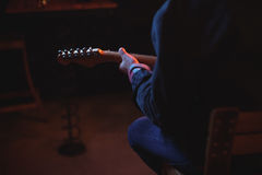 Mid-section of man playing guitar. In pub Royalty Free Stock Photo