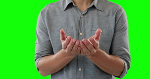 Mid-section of man pretending to be holding an invisible object. Against green background stock footage