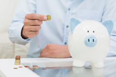 Mid section of a man putting some coins into a piggy bank Royalty Free Stock Photos