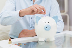 Mid section of a man putting some coins into a piggy bank. Closeup mid section of a man putting some coins into a piggy bank at home stock photography