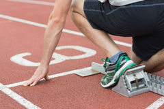 Mid section of a man ready to race on running track. Closeup mid section of a young man ready to race on running track Royalty Free Stock Images