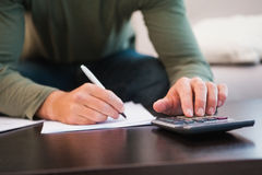 Mid section of man taking notes and using calculator stock photography