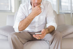Mid section of man text messaging at home Stock Photography