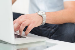 Mid section of a man using laptop on coffee table Stock Photo